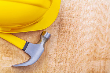 yellow hardhat and claw hammer on vintage wooden board copyspace