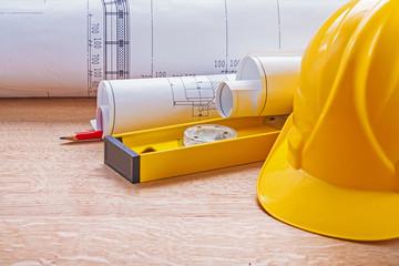 yellow helmet level blueprints pencil on wooden board constructi