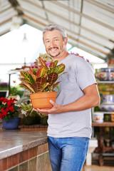 Mann steht mit Pflanze im Gartencenter