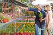 Gärtner vor Blumenladen hilft Kundin