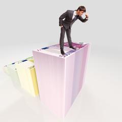 Geschäftsmann steht auf Berg vor Geld und schaut in die Tiefe