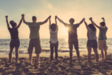 Group of people with raised arms at seaside, blurred background