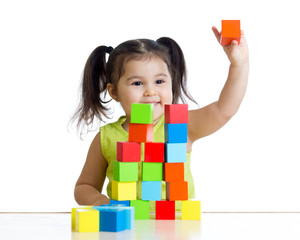 kid plays with building blocks and shows red cube