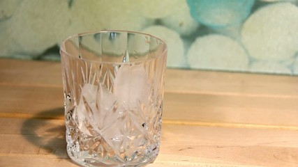 Man's hand throwing ice cubes and  pours  whiskey  in a glass