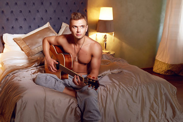 Handsome sexy man naked torso in bedroom playing guitar romance