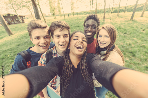 Leinwanddruck Bild Group of multiethnic teenagers taking a selfie at park