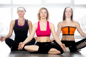 Group of three females meditating in class