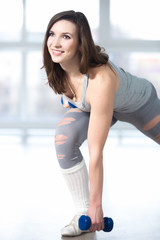 Sporty young woman doing lunges with dumbbells