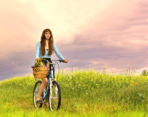Happy beautiful woman rides a bicycle on a summer meadow