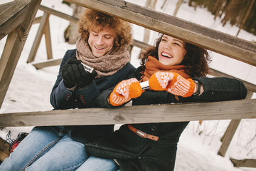Couple playing harmonica together in winter outdoors