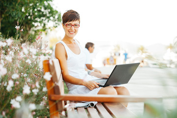 Young casual happy woman with laptop outside