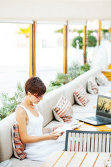 Young casual happy woman reading magazine outside