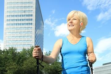 Dame beim Walken in der Stadt mit Kopfhoerer