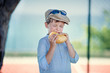 Cute little boy with pleasure eats hamburger
