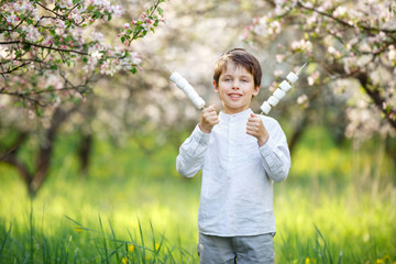 Happy boy with marshmallow in blooming garden