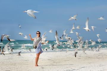 Young beautiful woman watching the seagulls flying