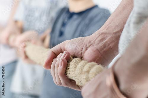 Kinder ziehen am Seil gegen Eltern - 78604244