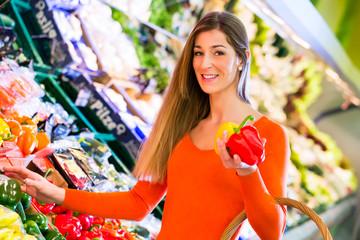 Frau wählt Gemüse im Lebensmittelmarkt aus