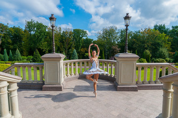 Ballerina dancing at park, standing in pointe position. Outdoors