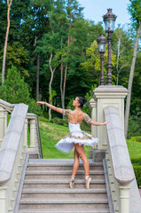 Ballerina stands on stairs, in pointe position. Outdoors