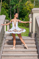 Ballerina stands on stairs, standing in pointe position.