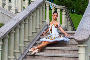Ballerina sits on stairs, standing in pointe position.