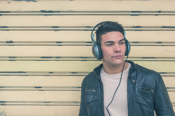 Young handsome man with headphones posing in the city streets