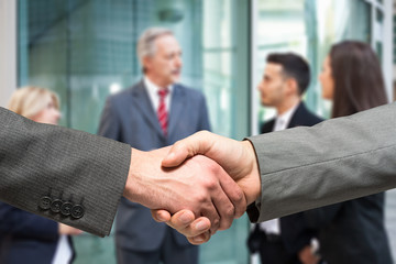 Business handshake. People talking in the background