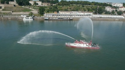 Aerial view on river boat firefighters in action.