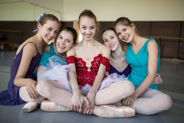 Five young ballerinas sitting on the floor and looking to the ca