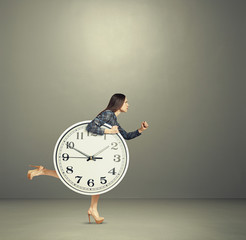 woman holding big clock and running