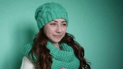 Beautiful girl in a turquoise knitted hat posing