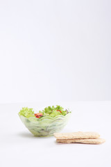 a bowl of fresh salad and crisps on white background