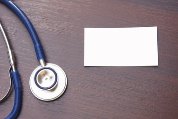 A blank and a blue stethoscope on a desktop from above