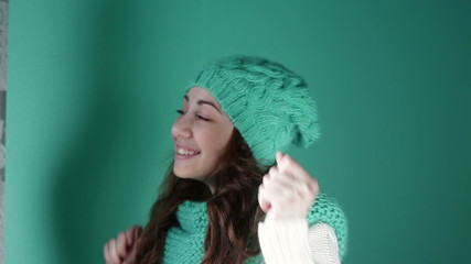 girl in a turquoise knitted hat dancing in the studio