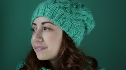Beautiful girl in a turquoise knitted hat nods
