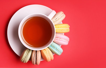 Colorful French Macaroons with Cup of Tea on red background