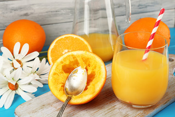 Glass of orange juice with slices, flowers and straws