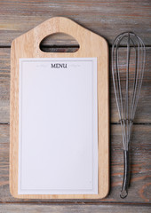 Cutting board with Menu sheet of paper with egg whisk