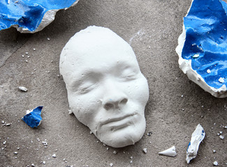 Plaster face mask in the middle of pieces of broken matt