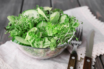 Cress salad with sliced cucumber and greens in glass bowl with