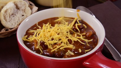 Sprinkling cheddar cheese on a bowl of chili