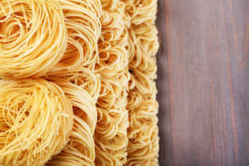 Different dry instant noodles on wooden background
