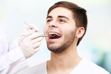 Examine of young man by dentist on light blurred background