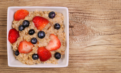 Oatmeal with berries on wooden background