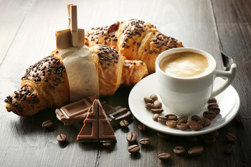 Fresh and tasty croissants with chocolate and cup of coffee