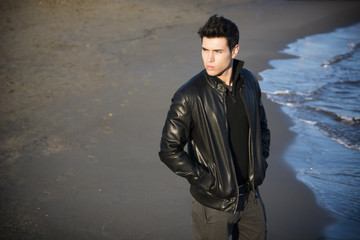Attractive young man at the seaside on the beach wearing black