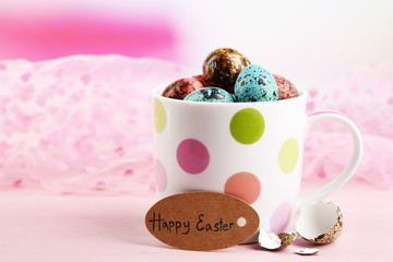 Bird colorful eggs in mug on bright background