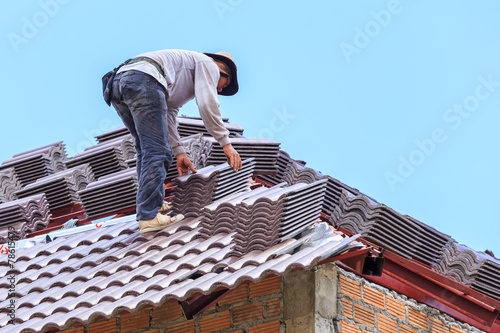 roof under construction with stacks of roof tiles for home build - 78615479