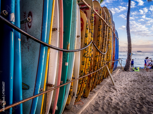 Colourful surfboards stacked up on Waikiki Beach at sunset. - 78615607